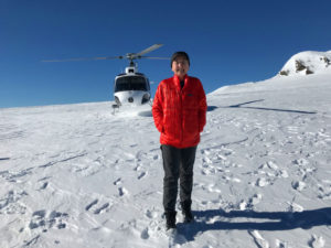 Mary on a glacier with helicopter behind her