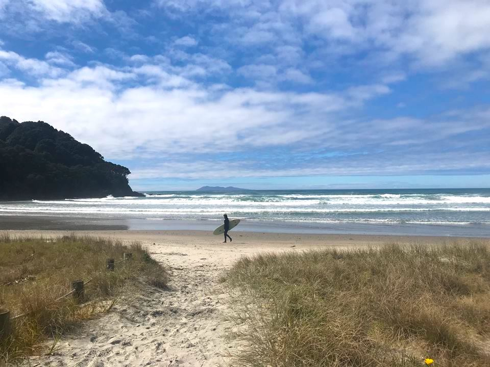 Lone surfer walking along Waihi Beach