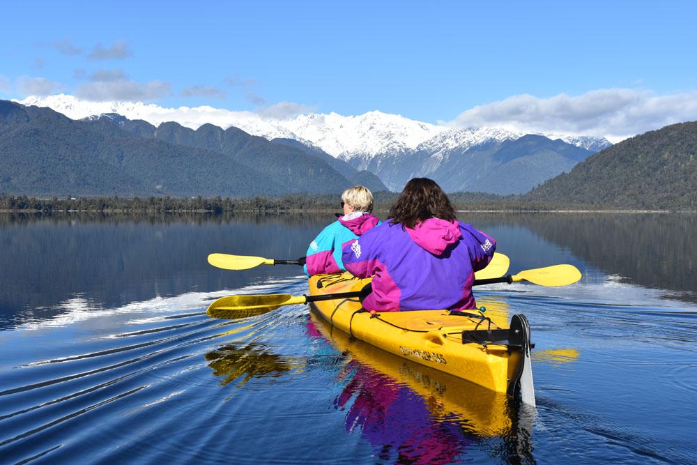 women in kayak with mountain views